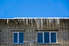 长的冰柱和雪吊在房子屋顶的房檐 图库摄影