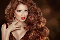 长的卷曲红色头发。美丽的时尚妇女画象。秀丽Mo 免版税图库摄影