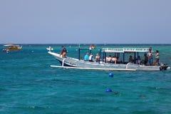 长的小船的潜水者在蓝色海 免版税库存图片