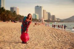 长的展示大帽子的亭亭玉立的女孩在反对城市海的海滩 免版税库存照片