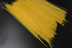 长的干细面条,从硬质小麦品种的意大利面团意粉在有趣的黑背景的组装 图库摄影