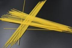 长的干细面条,从硬质小麦品种的意大利面团意粉在有趣的黑背景的组装 库存图片