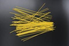 长的干细面条,从硬质小麦品种的意大利面团意粉在有趣的黑背景的组装 免版税库存图片