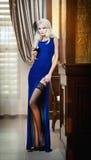 长的庄重装束的年轻美丽的豪华妇女。拿着一杯酒的蓝色礼服的美丽的年轻白肤金发的妇女 免版税库存照片
