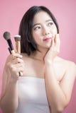 长的应用在光滑的面孔的头发亚裔年轻美丽的妇女化妆粉末刷子在桃红色背景 自然的构成 库存图片
