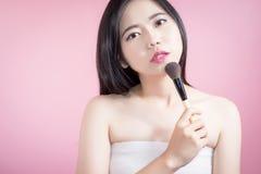 长的应用在光滑的面孔的头发亚裔年轻美丽的妇女化妆粉末刷子在桃红色背景 自然的构成 免版税图库摄影