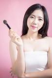 长的应用在光滑的面孔的头发亚裔年轻美丽的妇女化妆粉末刷子被隔绝在桃红色背景 自然的构成 库存照片