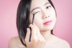 长的应用在光滑的面孔的头发亚裔年轻美丽的妇女化妆粉末刷子被隔绝在桃红色背景 自然的构成 免版税图库摄影