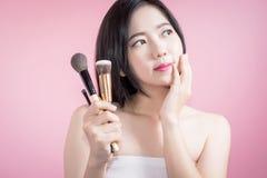 长的应用在光滑的面孔的头发亚裔年轻美丽的妇女化妆粉末刷子被隔绝在桃红色背景 自然的构成 库存图片