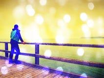 长的旅游痣的,秋天寒冷早晨人 扶手栏杆的游人 弄湿木板,在光滑的海上的constrution 免版税库存照片