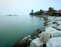 长的曝光射击了与美丽的岩石的海景在horizo 免版税库存图片