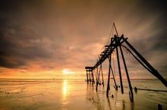 长的曝光射击,与美好的日落日出的老水泵塔与剧烈的云彩 免版税库存图片