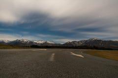 长的曝光街道、山和天空 库存照片