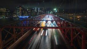 长的曝光timelapse录影:在布鲁克林大桥的交通汽车 反对夜都市风景NYC 免版税库存图片