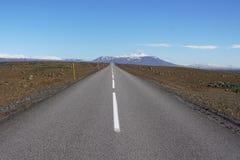 长的柏油路F35在中央冰岛在棕色领域之间和在高冰岛山前面 免版税图库摄影