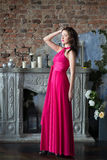 长的桃红色礼服的高雅妇女 豪华,室内 免版税库存照片