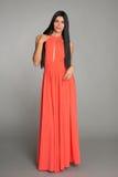 长的橙色礼服的美丽的少妇 免版税库存照片