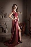长的深紫红色鞋带礼服的可爱的妇女 库存图片