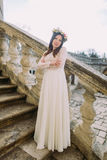 长的白色站立在老石台阶的婚礼礼服和花卉花圈的迷人的年轻新娘 免版税库存图片