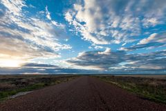 长的直路充分消失入遥远的天际在日落天空下云彩在澳洲内地 免版税库存图片