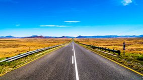 长的直路通过半沙漠南部非洲的干旱台地高原地区的不尽的大开风景在自由州和东开普省省的 免版税图库摄影