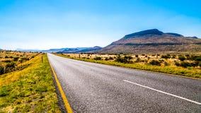 长的直路通过半沙漠南部非洲的干旱台地高原地区的不尽的大开风景在自由州和东开普省省的 免版税库存图片