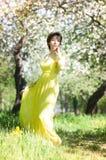 长的礼服的妇女在开花苹果公园 春天 免版税库存图片
