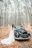 长的礼服的新娘在落的叶子站立在一辆减速火箭的汽车前 免版税库存图片