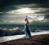 长的礼服的白肤金发的妇女在风雨如磐的海运 库存照片