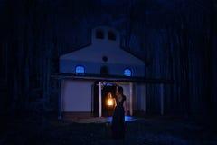 长的礼服的美丽的女孩有灯笼的单独在黑暗的森林里 免版税库存照片