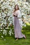 长的礼服boho样式的美丽的少妇在绿草联合国 库存照片