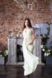 长的米黄礼服的高雅妇女 在内部 免版税库存图片