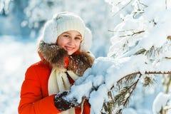长的红色的美丽的十几岁的女孩在夹克白色帽子和围巾下有乐趣外部在与雪的木头在冬天 免版税库存图片