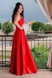长的红色礼服的女孩用在摆在在一个木地板上的庭院阳台的臀部的手 免版税库存照片