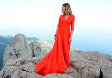 长的红色礼服的妇女在山的峭壁边缘 Ai陪替氏山峰顶  图库摄影