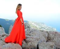 长的红色礼服的妇女在山的峭壁边缘 Ai陪替氏山峰顶  免版税库存照片