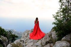 长的红色礼服的妇女在山的峭壁边缘 Ai陪替氏山峰顶  免版税图库摄影