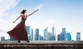 长的红色礼服的瞎的妇女在大厦顶部 混合画法 库存照片