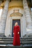 长的红色礼服立场的妇女在台阶 免版税库存图片
