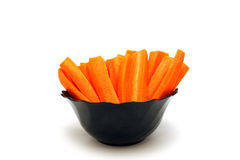 长的红萝卜切片到碗里 免版税库存照片