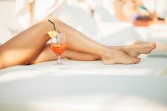 长的腿和热带鸡尾酒 免版税库存图片