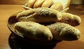 长的芝麻小圆面包、圆的卷和切的面包在柳条筐 库存图片