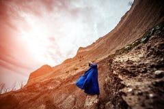 长的蓝色礼服的妇女在沙子峡谷 库存图片