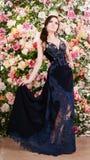 长的蓝色鞋带礼服的美丽的妇女在花背景 方式 免版税库存图片