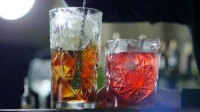 长的酒吧匙子混合从科涅克白兰地的冰在未聚焦的背景的玻璃 股票视频