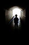 长的隧道走道的年轻男孩 免版税库存照片