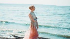 长的飞行的桃红色礼服闪动的立场的孤独的旅客在蓝色海的岸,认为,拥抱与 影视素材
