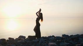 长的黑礼服跳舞的无忧无虑的妇女在日落的海滩 股票录像