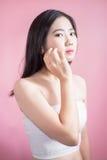 长的头发亚洲年轻美丽的妇女十字架胳膊和点手指向上被隔绝在桃红色背景 自然构成,温泉疗法 免版税库存照片