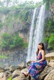 长的头发女孩在瀑布附近坐 免版税库存图片